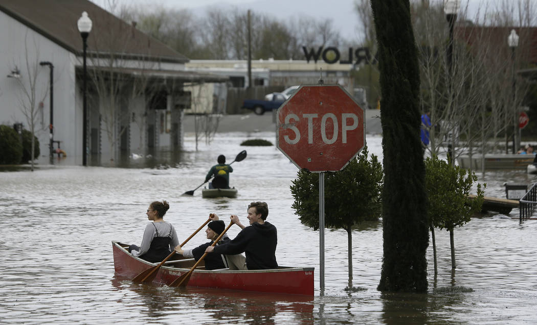 People paddle and row through the flooded Barlow Market District Wednesday, Feb. 27, 2019, in Sebastopol, Calif. (Eric Risberg/AP)