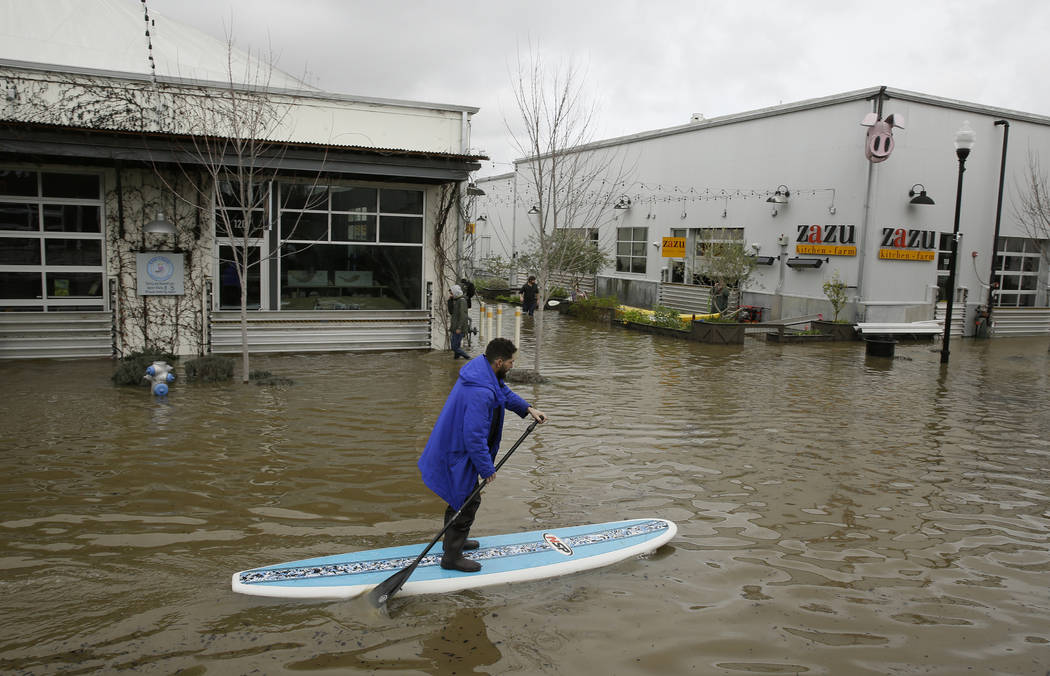 A man uses a paddle board to make his way through the flooded Barlow Market District Wednesday, Feb. 27, 2019, in Sebastopol, Calif. (Eric Risberg/AP)