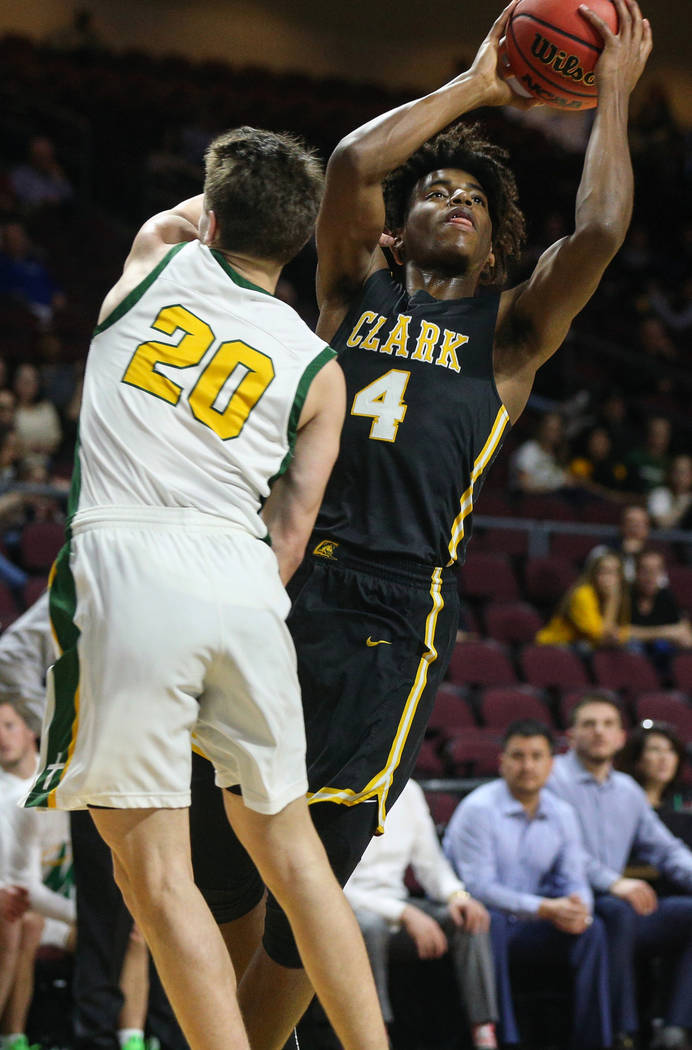 Clark's Carlos Allen (4) looks to take a shot while being guarded by Bishop Manogue's Cort Ballinger (20) during the first half of a Class 4A state boys basketball semifinal game at the Orleans Ar ...
