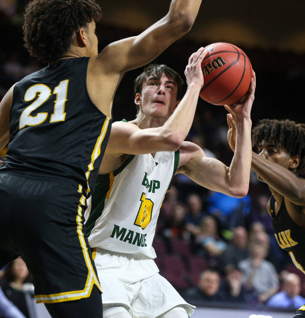 Bishop Manogue's Kolton Frugoli looks to take shot while being guarded by Clark's Jalen Hill (21) during the second half of a Class 4A state boys basketball semifinal game at the Orleans Arena in ...