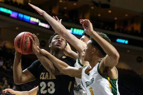 Clark's Antwon Jackson (23) looks to take a shot while being guarded by Bishop Manogue's Joshua Rolling (1) and Daniel Bansuelo (3) during the first half of a Class 4A state boys basketball semif ...