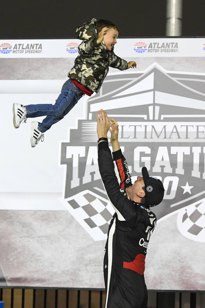 Kyle Busch tosses his son Brexton up in the air while celebrating in Victory Lane after winning the NASCAR Truck Series auto race at Atlanta Motor Speedway, Saturday, Feb. 23, 2019, in Hampton, Ga ...