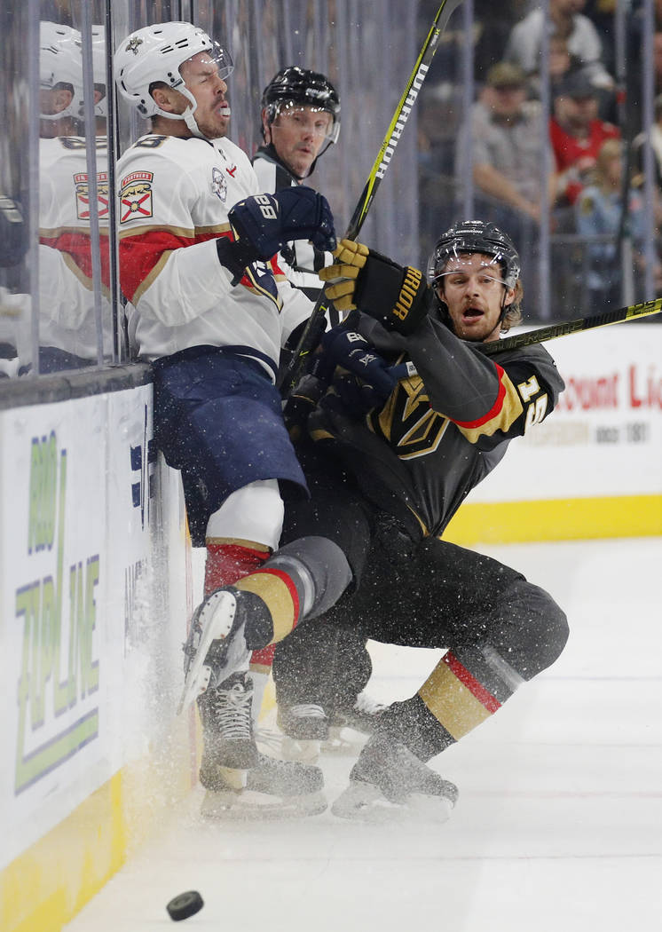 Vegas Golden Knights defenseman Jon Merrill (15) checks Florida Panthers center Jayce Hawryluk (8) into the boards during the first period of an NHL hockey game Thursday, Feb. 28, 2019, in Las Veg ...