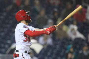 Washington Nationals Bryce Harper (34) follows the ball as he hits his 100th RBI during the fourth inning of a baseball game against the Miami Marlins in Washington, Monday, Sept. 24, 2018. (AP Ph ...
