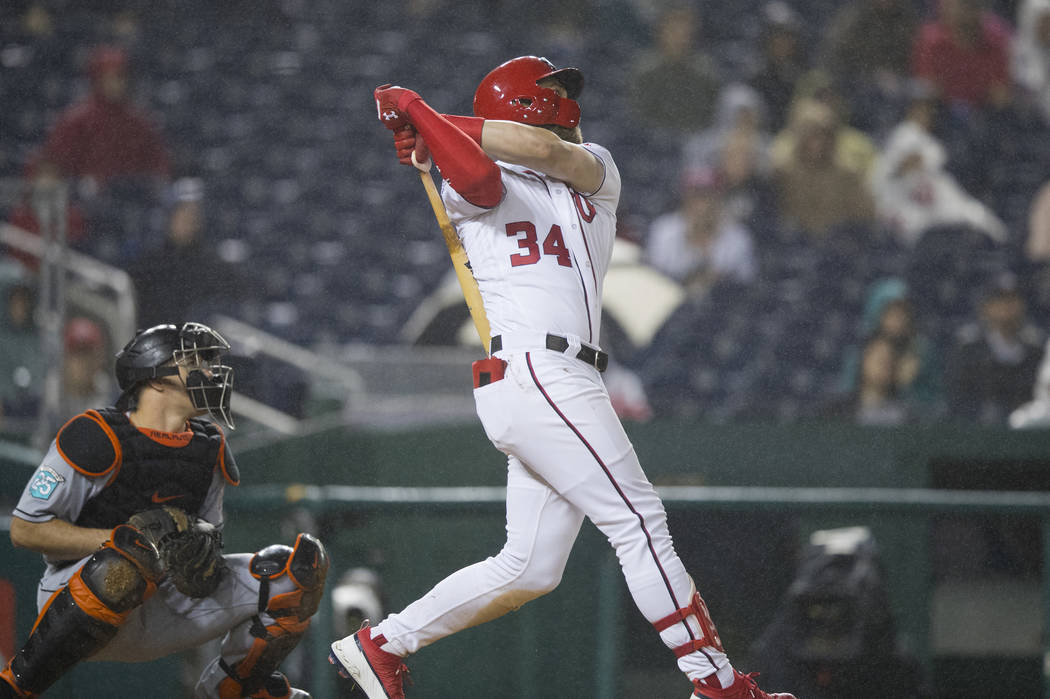 Washington Nationals Bryce Harper (34) follows the ball as he hits his 100th RBI, during the fourth inning of a baseball game against the Miami Marlins in Washington, Monday, Sept. 24, 2018. (AP P ...