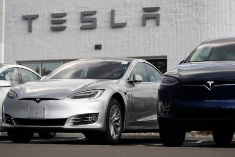 In this Sunday, July 8, 2018, photograph, 2018 Model 3 sedan sits next to a Model X on display outside a Tesla showroom in Littleton, Colo. (AP Photo/David Zalubowski)