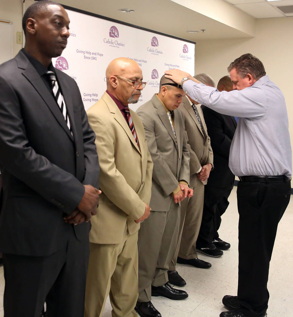 Deacon Thomas Roberts, president and chief executive officer of Catholic Charities, blesses graduates Broderick Gray, left, Theodore Hines, Derrick Johnson, center, Ricky Delucia, and John Bontemp ...