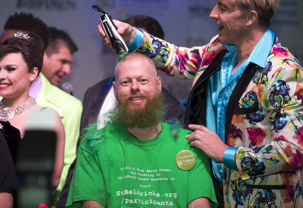 Ed Conte, a crew member for Cirque du Soleil's Zumanity, gets his head shaved during the St. Baldrick's head-shaving event to raise money for childhood cancer research outside the New York-New Yor ...