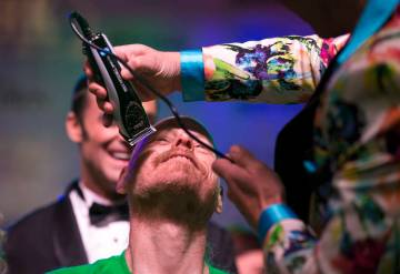"""Ed Conte, a crew member for Cirque du Soleil's """"Zumanity,"""" gets his head shaved during the St. Baldrick's head-shaving event to raise money for childhood cancer research outside the New York-New Y ..."""