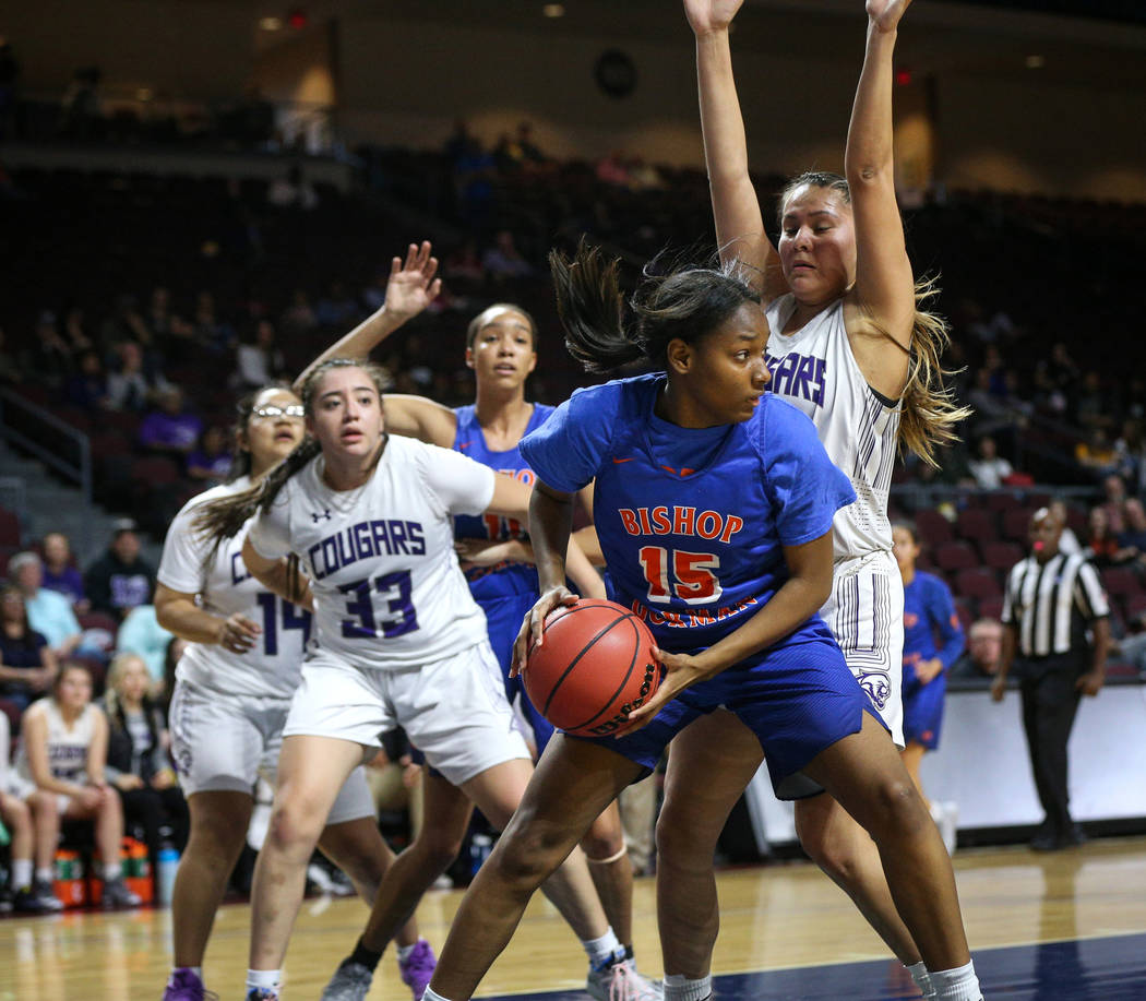 Bishop Gorman's Asya Bey (15) protects the ball while being guarded by Spanish Springs' Lauryn Dressler (20) during the first half of a Class 4A state girls basketball semifinal game at the Orlean ...