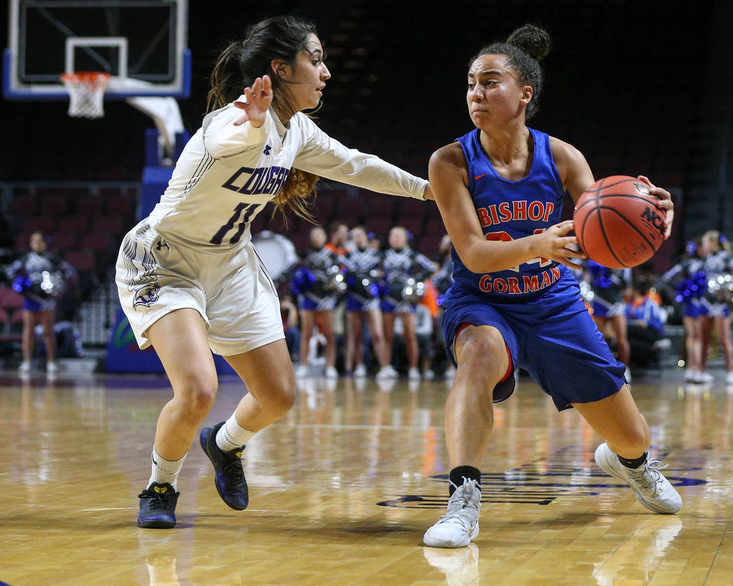 Bishop Gorman's Bentleigh Hoskins (24) looks to pass the ball while being guarded by Spanish Springs' Naelia Pinedo (11) during the first half of a Class 4A state girls basketball semifinal game a ...