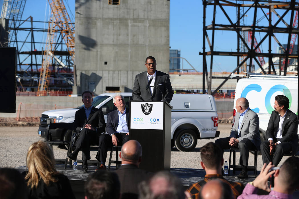 Derrick Hill, center, vice president for Cox Business, speaks during a press conference at the Raiders stadium construction site in Las Vegas, Thursday, Feb. 28, 2019. Cox Communications is becomi ...