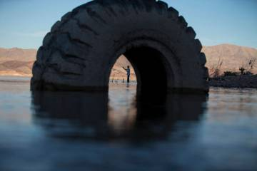 Ivan Lau of Las Vegas is seen through a partially submerged tire as he fishes near Boulder Harbor at Lake Mead National Recreation Area on Wednesday, Sept. 26, 2018. Richard Brian Las Vegas Review ...