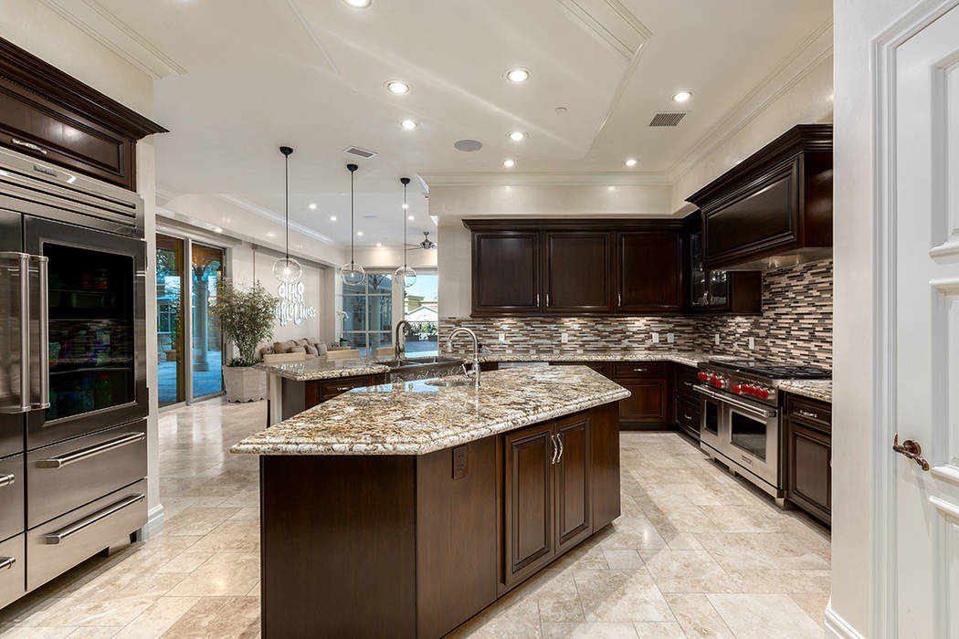 The kitchen is equipped with upgraded professional-grade, stainless steel appliances, dark wood ...