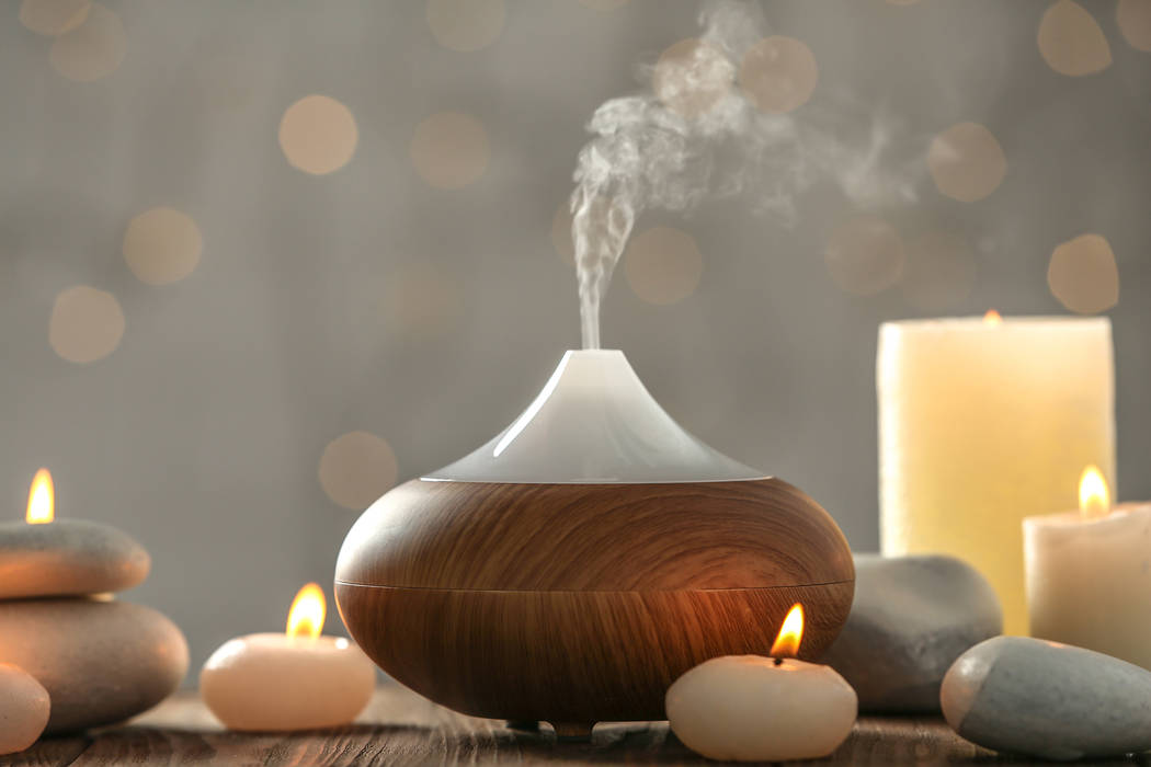 An aroma oil diffuser and candles are used to inject scent into a home. (Getty)