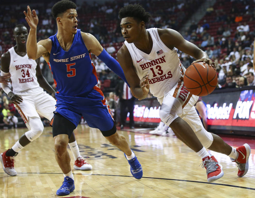 UNLV Rebels guard Bryce Hamilton (13) drives to the basket against Boise State Broncos guard Malek Harwell (5) during the first half of a basketball game at the Thomas & Mack Center in Las Veg ...