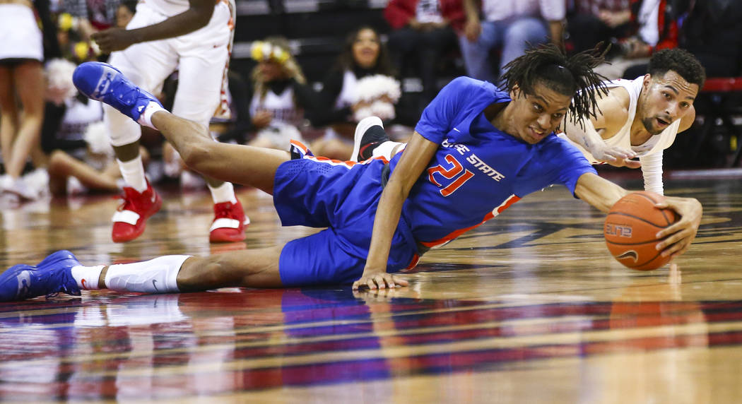 Boise State Broncos guard Derrick Alston (21) and UNLV Rebels guard Noah Robotham battle for a loose ball during the second half of a basketball game at the Thomas & Mack Center in Las Vegas o ...