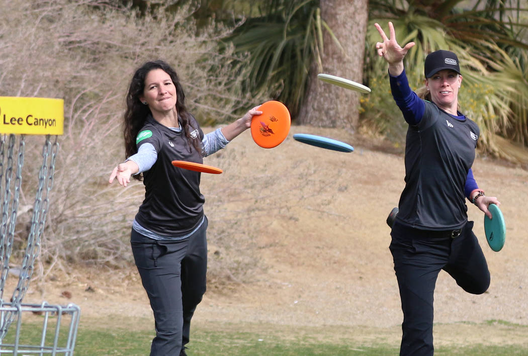 Madison Walker of Pensacola, Fla., left, and Ellen Widboom of Brooksville , Fla., attempt to throw their discs into the basket during practice at Wildhorse Golf Club on Wednesday, Nov. 20, 2019, ...