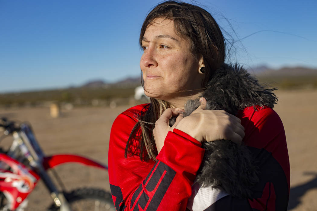 Angie Wright holds her dog Phoenix at Western Raceway track outside White Hills, Arizona, Sunday, Feb. 24, 2019. Wright will be racing in the Mint 400's motorcycle race, the first dirt bike race f ...