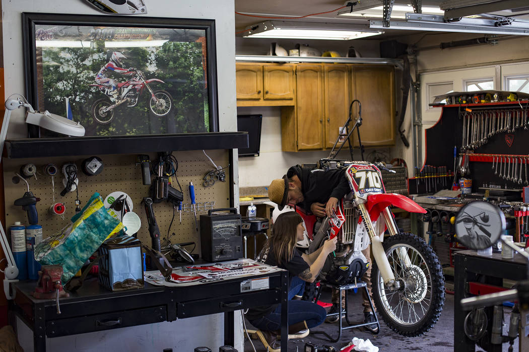 Angie Wright works on her bike with her boyfriend Derek Stephens at her father's home in Henderson, Wednesday, March 6, 2019. Wright will be racing in the Mint 400, the first dirt bike race for th ...