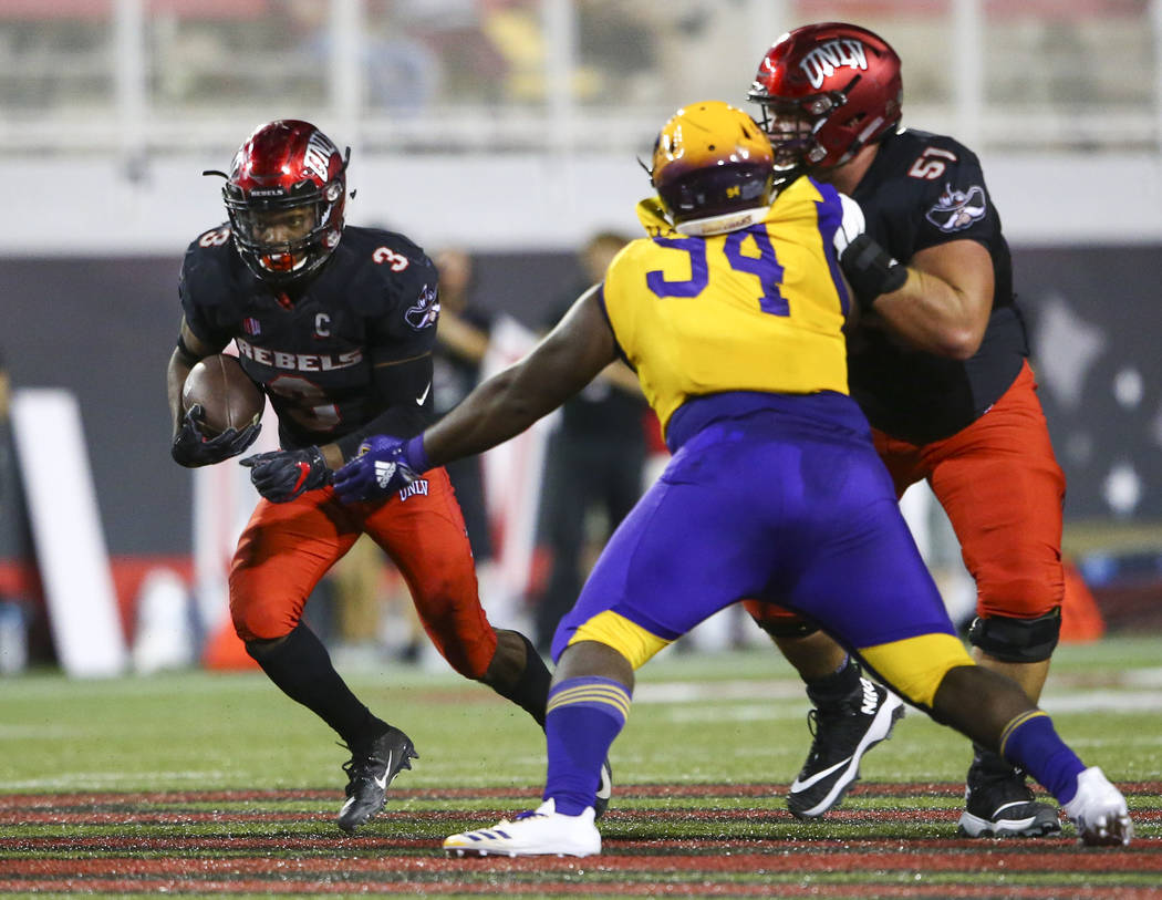 UNLV Rebels running back Lexington Thomas (3) runs the ball past Prairie View A&M Panthers defensive lineman Jermaine Jackson (94) in front of UNLV Rebels offensive lineman Zack Singer (51) du ...