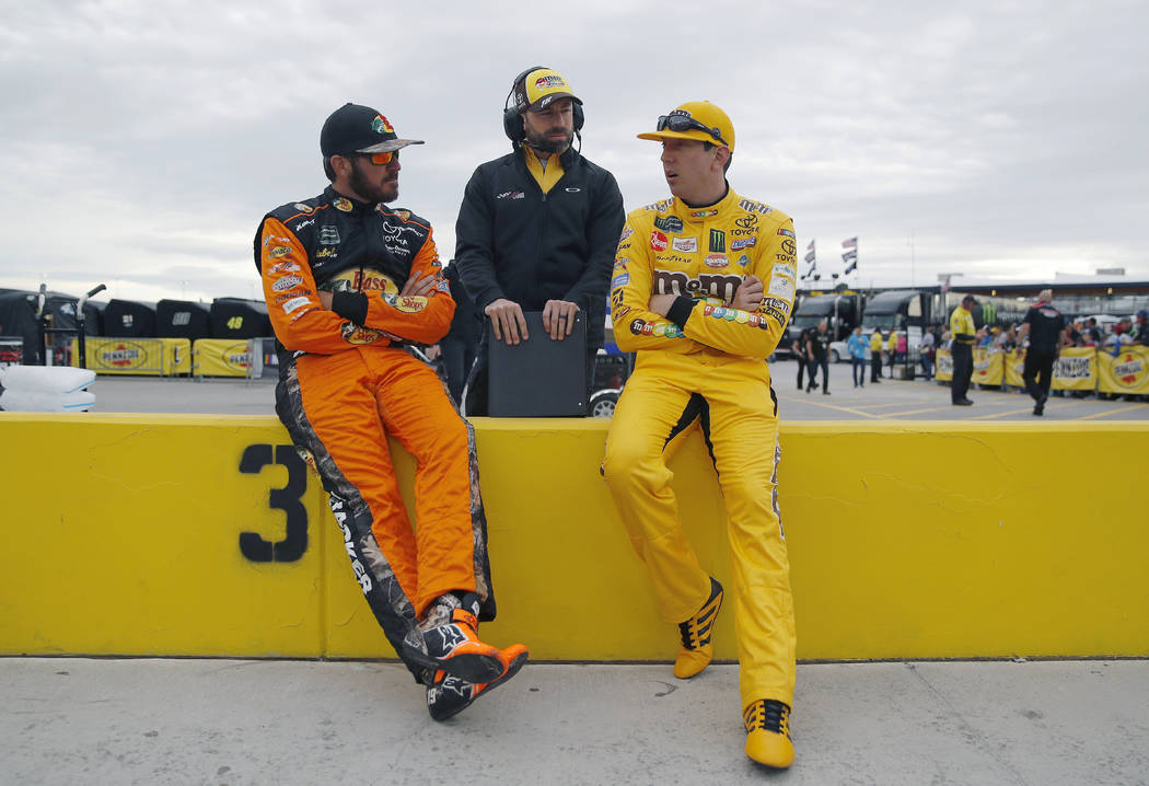 Martin Truex Jr., left, and Kyle Busch, right, talk before qualifying for a NASCAR Cup Series auto race at the Las Vegas Motor Speedway, Friday, March 1, 2019, in Las Vegas. (AP Photo/John Locher)