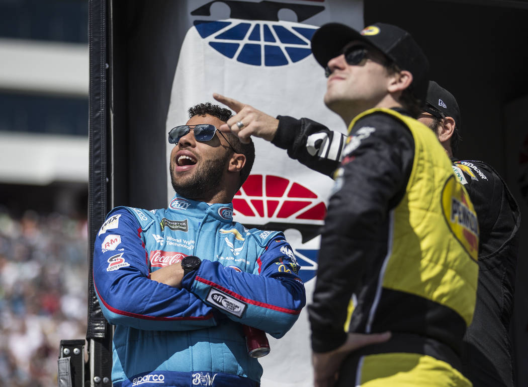 Bubba Wallace, left, watches the United States Air Force Thunderbirds make a pass above Las Vegas Motor Speedway before the start of the Monster Energy NASCAR Cup Series Pennzoil 400 on Sunday, Ma ...