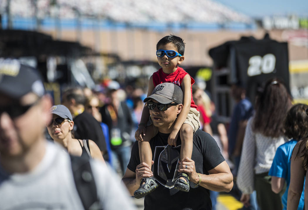 Robert Chavez carries son Ray, 5, in pit row before the start of the Monster Energy NASCAR Cup Series Pennzoil 400 on Sunday, March 3, 2019, at Las Vegas Motor Speedway, in Las Vegas. (Benjamin Ha ...