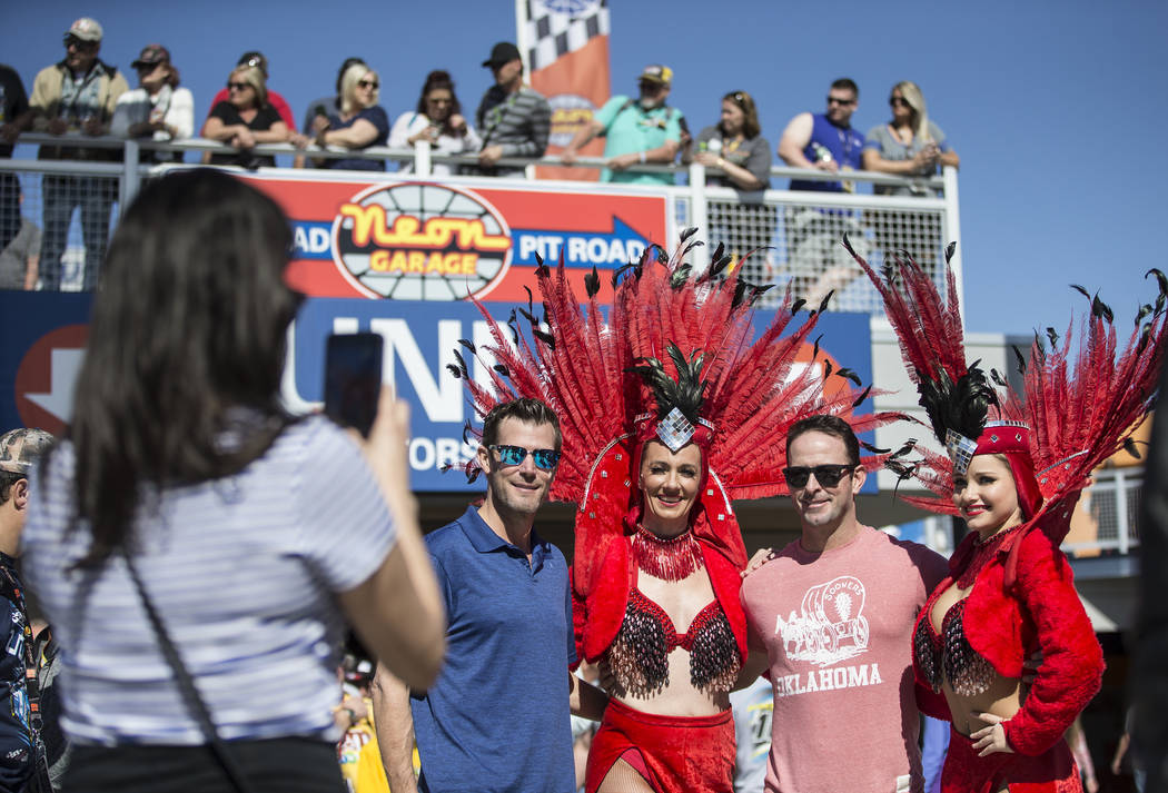 Shane O'Toole, left, and Bryan Baker take a photo with showgirls at the Monster Energy NASCAR Cup Series Pennzoil 400 on Sunday, March 3, 2019, at Las Vegas Motor Speedway, in Las Vegas. (Benjamin ...