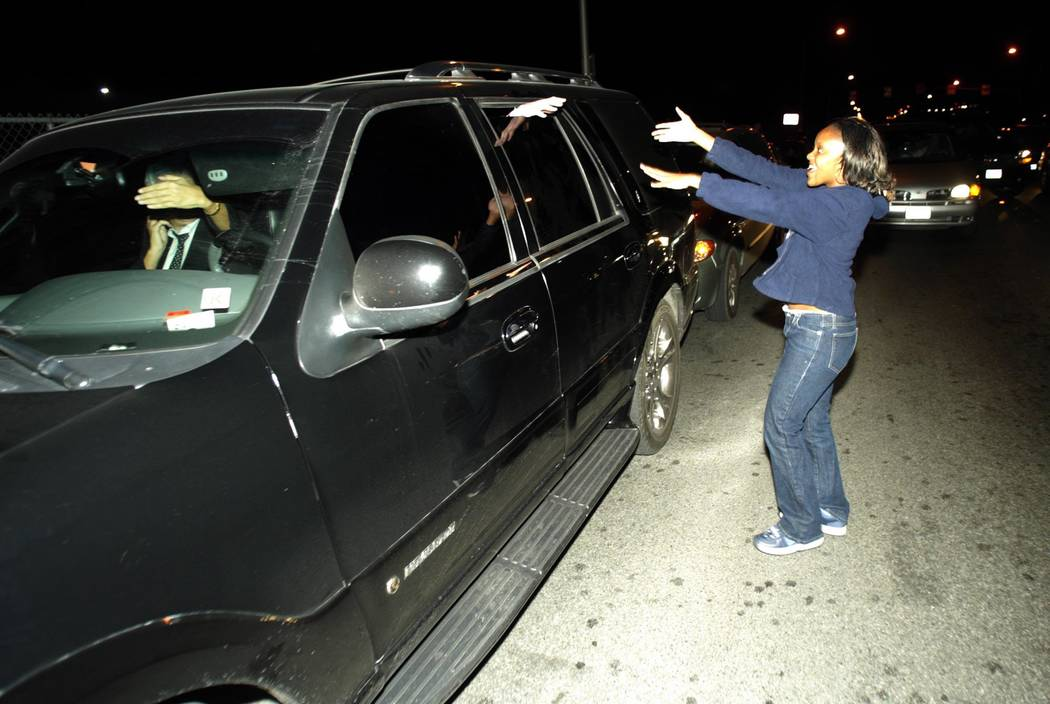 A Michael Jackson fan tries to touch the pop superstar through the window of his car Thursday, Nov. 20, 2003, after Jackson arrived back in Las Vegas after posting bail in Santa Barbara on child m ...
