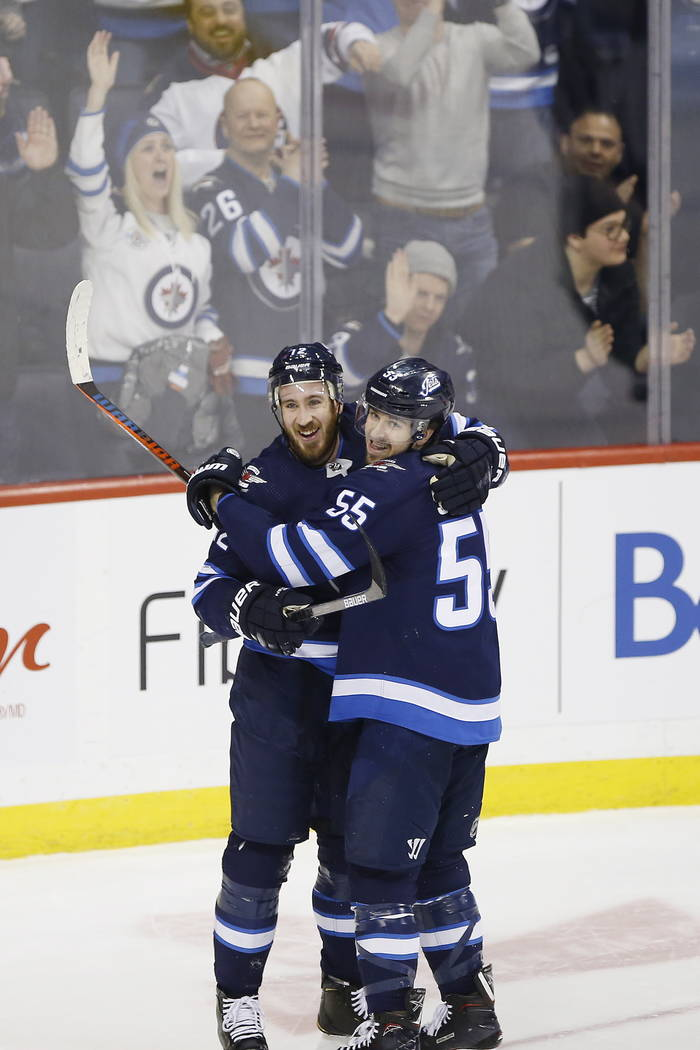 Winnipeg Jets' Kevin Hayes (12) and Mark Scheifele (55) celebrate Hayes' his first goal for the Jets since his recent trade to the team, during the third period of an NHL hockey game against the N ...