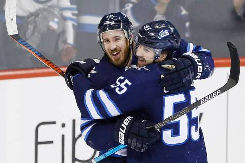 Winnipeg Jets' Kevin Hayes (12) and Mark Scheifele (55) celebrate Hayes' his first goal for the Jets since his recent trade to the team, against the Nashville Predators during the third period of ...
