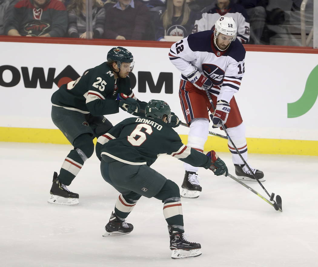 Winnipeg Jets' Kevin Hayes (12) plays the puck in front of Minnesota Wild Jonas Brodin (25) and Ryan Donato (6) during the first period of an NHL hockey game Tuesday, Feb. 26, 2019, in Winnipeg, M ...