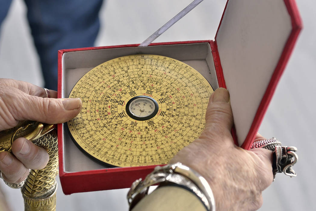 Doc Phineas Kastle demonstrates the use of the feng shui Luo Pan compass, a device to measure the energy or as Chinese refer to as chi or qi. (Bill Hughes/Real Estate Millions)