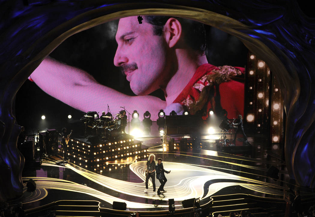 An image of Freddie Mercury appears on screen as Brian May, left, and Adam Lambert of Queen perform at the Oscars on Sunday, Feb. 24, 2019, at the Dolby Theatre in Los Angeles. (Photo by Chris Piz ...