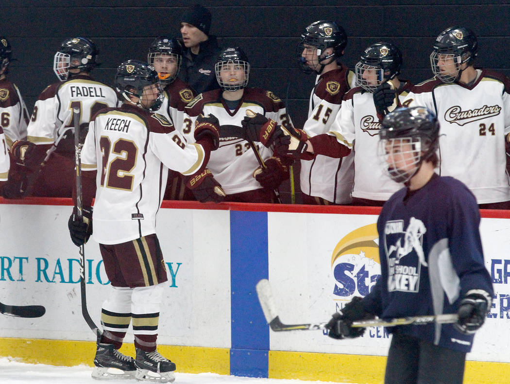Faith Lutheran's Hunter Keech (22) celebrates with his teammates after he scored a goal against Utah's goaltender during the first period of a hockey game at the City National Arena in Las Vegas, ...