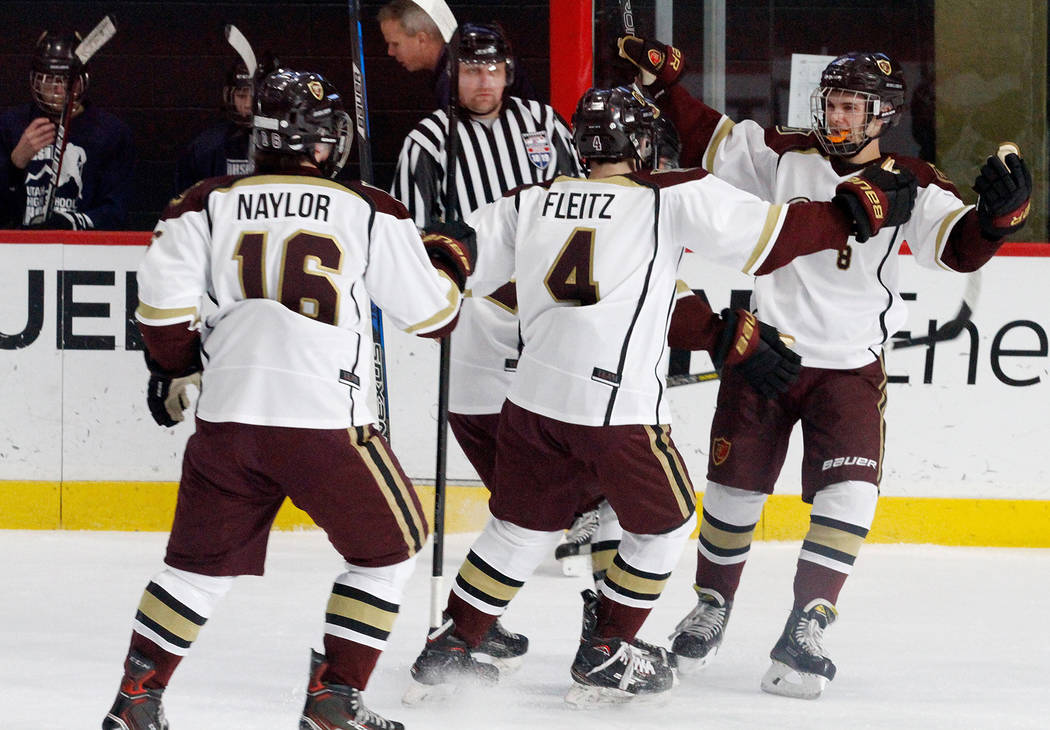 Faith Lutheran's Matty Johnson, right, celebrates with his teammates Colton Fleitz (4) and Joseph Naylor (16) after Johnson scored a goal against Utah's goaltender during the first period of a hoc ...