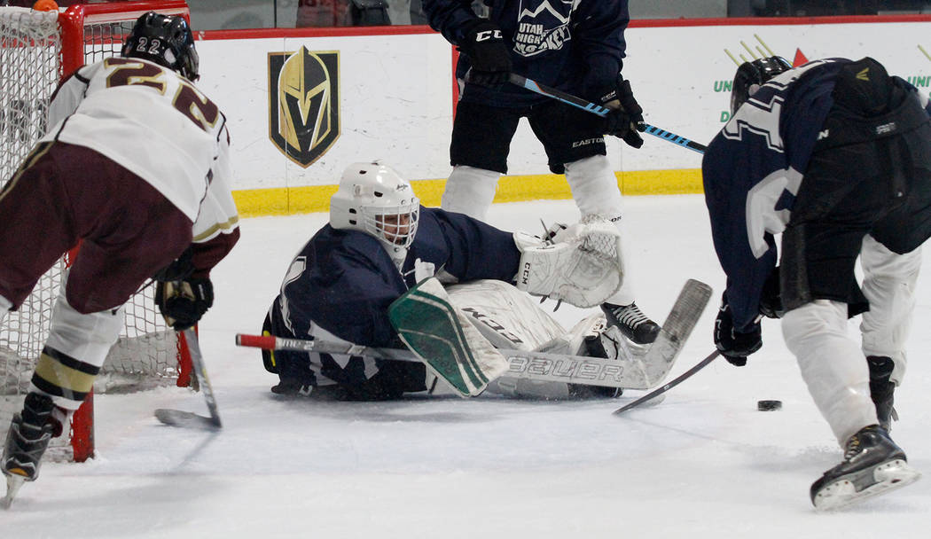 Utah's goaltender Landon Palmer, center, makes a save against Faith Lutheran's Hunter Keech (22) during the second period of a hockey game at the City National Arena in Las Vegas, Saturday, Dec. 1 ...