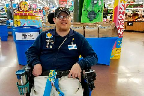 In this April 21, 2018 photo provided by Rachel Wasser, Walmart greeter John Combs works at a Walmart store in Vancouver, Wash. Combs, who has cerebral palsy, and other greeters with disabilities ...