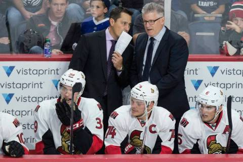 Ottawa Senators head coach Guy Boucher, left, speaks with assistant coach Marc Crawford during the third period of a preseason NHL hockey game in Halifax, Nova Scotia on Sept. 26, 2016. (Darren Ca ...