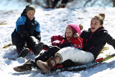 Lincoln Warnick, 10, from left, with his sisters Abby, 6, and Lydia, 12, play in the snow at Willows Park in Las Vegas, Friday, Feb. 22, 2019. (Erik Verduzco/Las Vegas Review-Journal) @Erik_Verduzco
