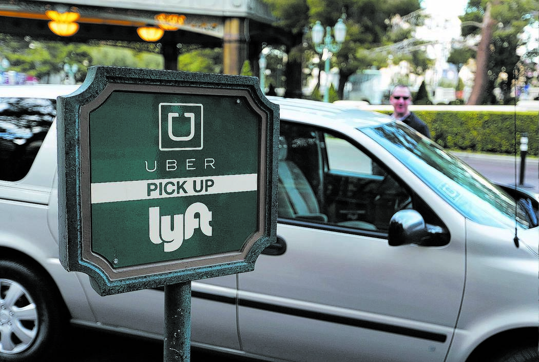 In this Jan. 14, 2016, photo, a driver waits to pick up passengers at an Uber and Lyft pick up area at the Bellagio hotel and casino in Las Vegas. The advent of Uber and Lyft in Nevada last fall h ...