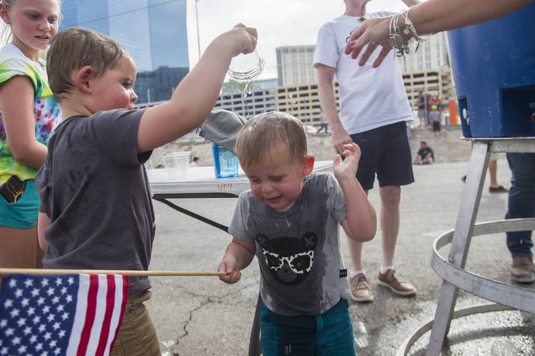 Sawyer Tuck, 4, pours water on his brother Oliver Tuck's head, 2, to cool down at the Evel Live event where Travis Pastrana attempted to exceed three of Evel Knievel's famous jumps in a lot behind ...