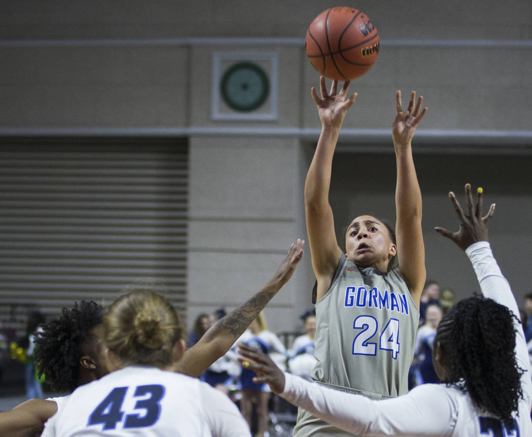 Bishop Gorman junior Bentleigh Hoskins (24) shoots a jump shot over Centennial senior Eboni Walker (22) and senior Bryar Tronnier (43) during the fourth quarter of the Class 4A girls state champio ...