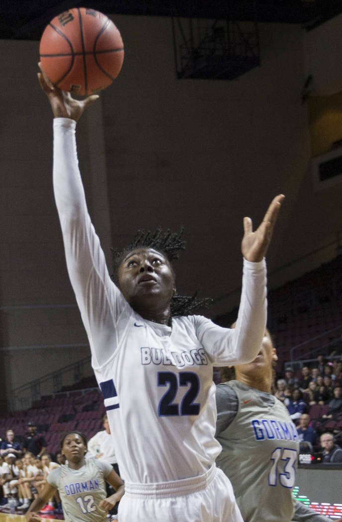 Centennial senior Eboni Walker (22) drives past Bishop Gorman senior Georgia Ohiaeri (13) in the second quarter of the Class 4A girls state championship game on Friday, March 1, 2019, at Orleans A ...