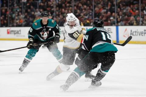 Vegas Golden Knights' Jonathan Marchessault, center, shoots as Anaheim Ducks' Adam Henrique defends during the first period of an NHL hockey game Friday, March 1, 2019, in Anaheim, Calif. (AP Phot ...