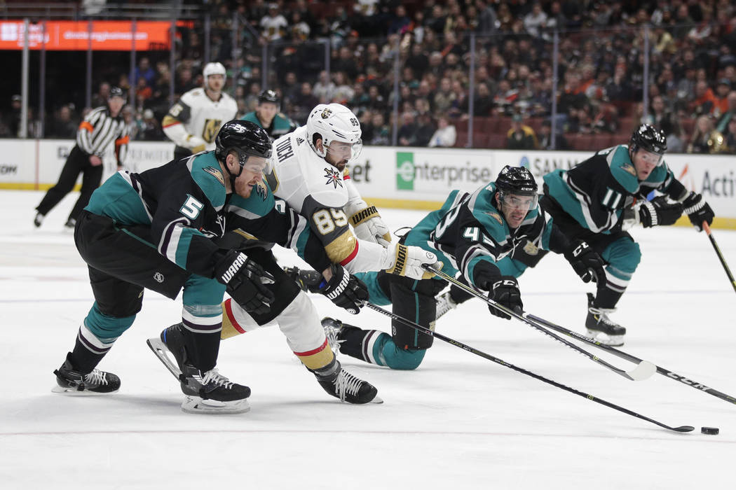 Vegas Golden Knights' Alex Tuch (89) fights for the puck with Anaheim Ducks' Korbinian Holzer (5) and Jaycob Megna (43) during the first period of an NHL hockey game Friday, March 1, 2019, in Anah ...