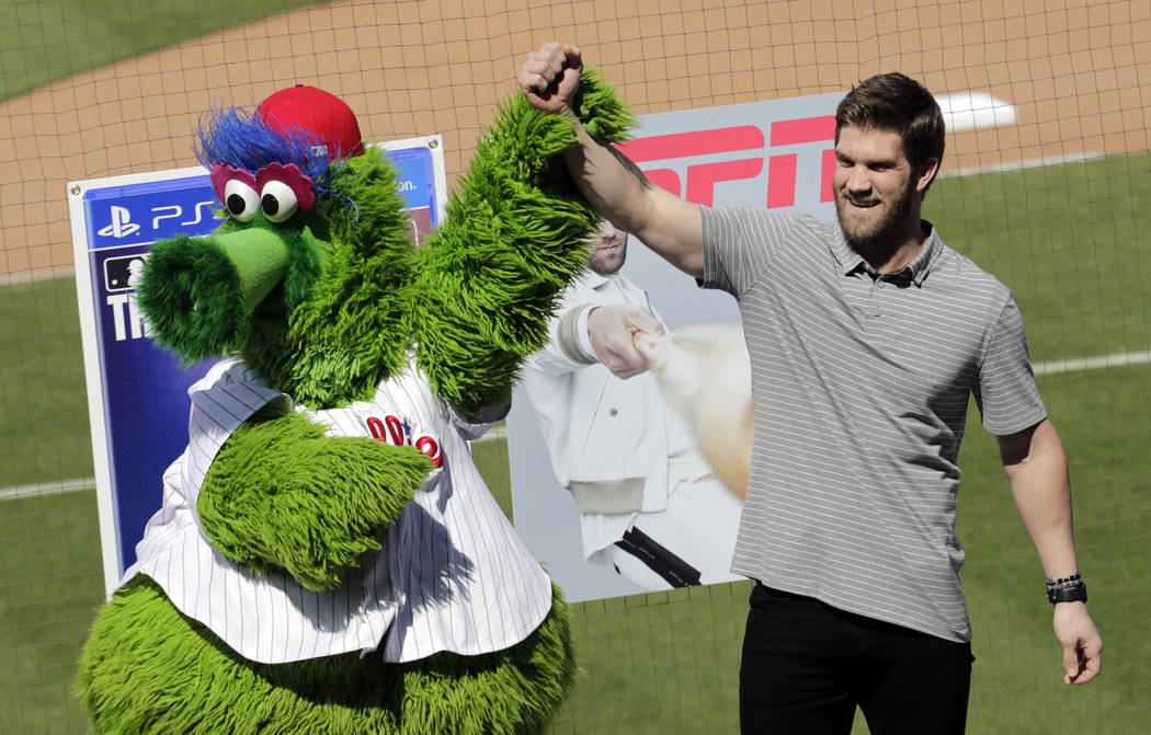 Bryce Harper stands with the Philadelphia Phillies mascot Phanatic before being introduced as a Phillies player during a news conference at the team's spring training baseball facility, Saturday, ...