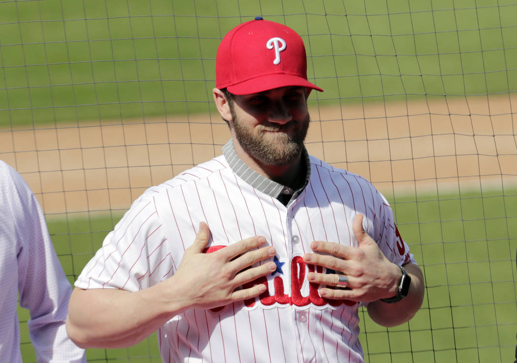 Bryce Harper smiles after putting on a Philadelphia Phillies jersey during a news conference at the team's spring training baseball facility, Saturday, March 2, 2019, in Clearwater, Fla. Harper an ...