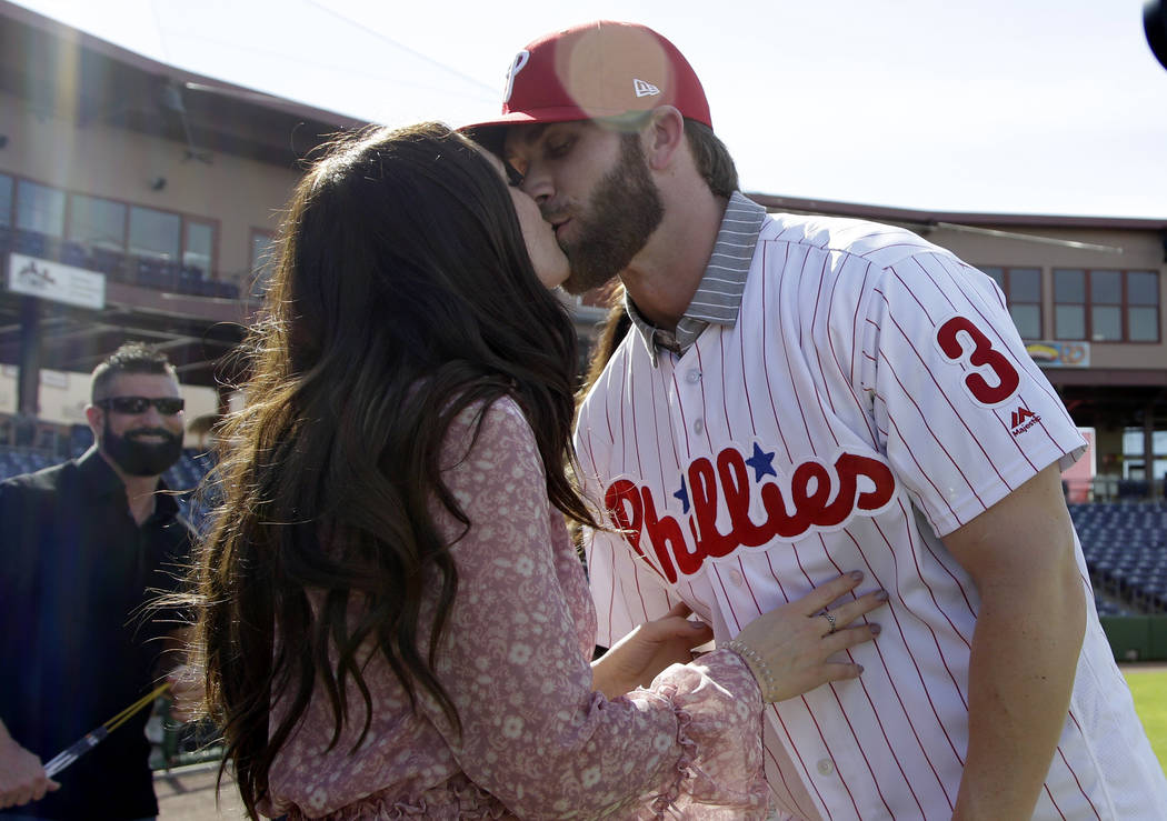 Bryce Harper, right, hugs his wife Kayla after being introduced as a Philadelphia Phillies player during a news conference at the team's spring training baseball facility, Saturday, March 2, 2019, ...